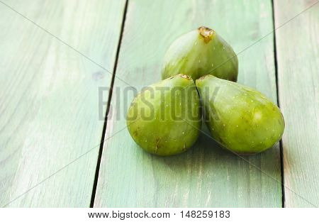 Whole three fresh green figs fruits on a wooden background