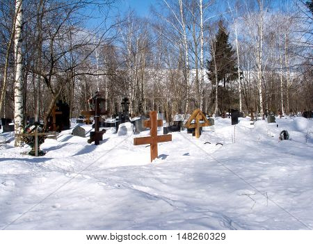 Winter landscape with suburban cemetery in deep snow