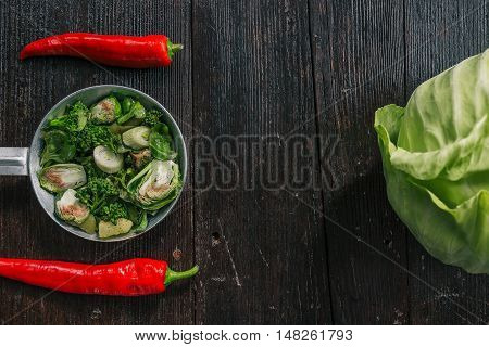 Green cabbage, broccoli, brussel sprouts and chili peppers on the dark wooden surface