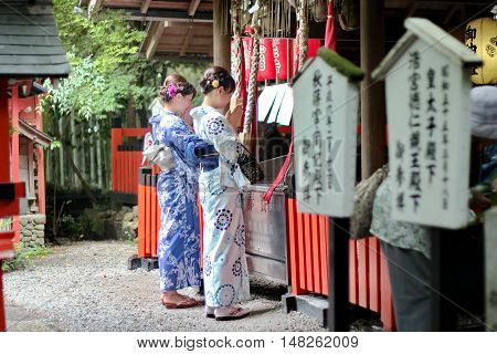 Kyoto,Japan-June 25,Two women's kimonos respect belief by beautiful mind within shrine at Arashiyama on June 25,2016 in Kyoto,Japan. Selective focus at wowen.