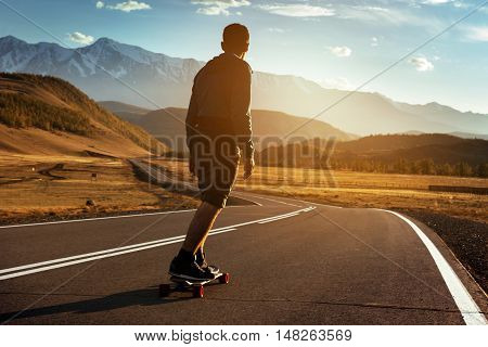 Man rides at straight road on longboard at sunset time
