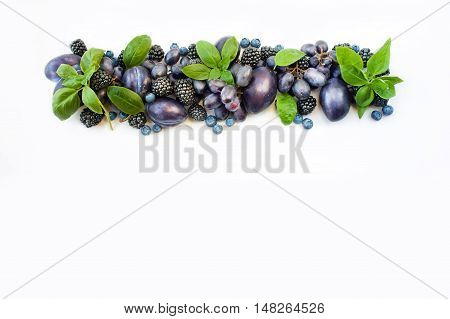 Group of fresh fruits and berries with basil's on a white background. Ripe blueberries grapes plums and blackberries. Top view with copy space.