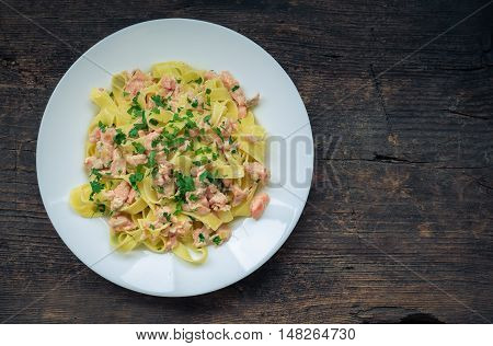 Italian Wholemeal Pasta Tagliatelle with Salmon and Parsley. Fresh pasta with smoked salmon in the sauce on old wooden background with place for text. Italian cuisine concept. Copy space. Top view.