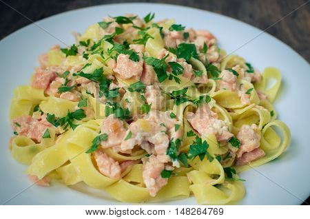 Italian Wholemeal Pasta Tagliatelle with Salmon and Parsley. Close up Fresh pasta with smoked salmon in the sauce on old wooden background. Italian cuisine concept. Selective focus.