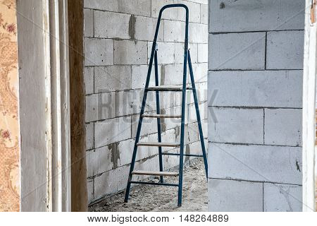 Stepladder in the dirty room during capital repair