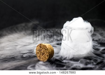 White Smoke Inside Glass Bottle At Black Background, Mistery Halloween Concept