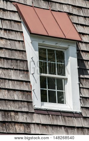 Attic window of pointed wooden roof of old house