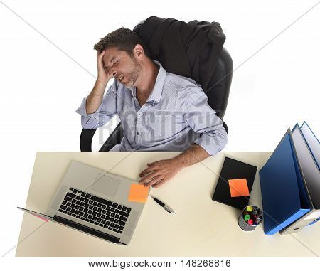 tired and frustrated businessman looking worried face expression suffering stress at office laptop computer having working long hours sitting on desk with paperwork isolated on white background