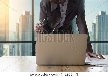 Business woman standing hand holding glasses and document finacial report wokring with laptop computer. selective focus on glasses.