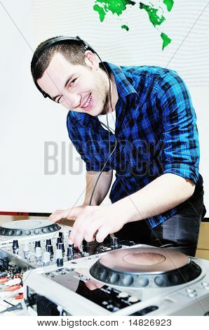 young dj man with headphones and compact disc dj equipment on party