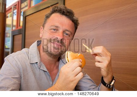 Man in a restaurant a hamburger he is hungry and having a good bite