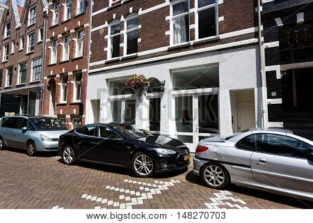 Amsterdam Netherlands - July 03 2016: Tesla car parked on a street nearby the traditional Dutch houses