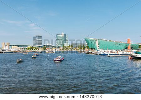 View of the River Amstel, houses and barges on a sunny day . Netherlands.