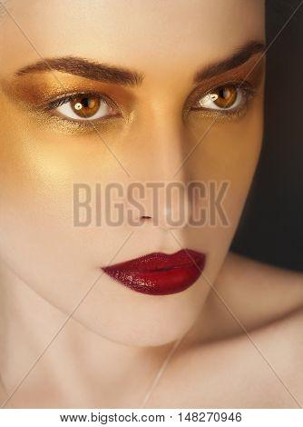 woman beauty with artistic golden makeup closeup portrait