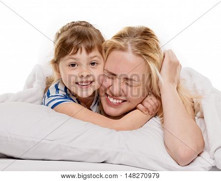 Portrait of a joyful mother and her little daughter in the bed on white background