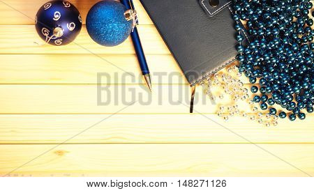 Christmas balls, decorations and ballpoint pen on a table