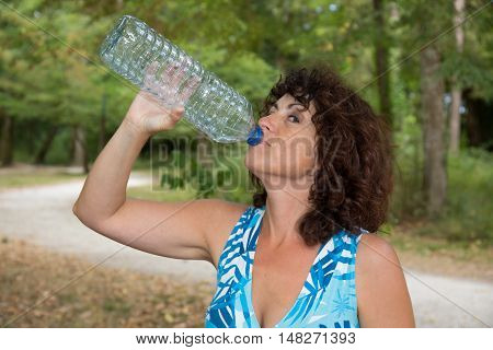 Dark-haired woman wearing blue t-shirt drinking water at summer green park.