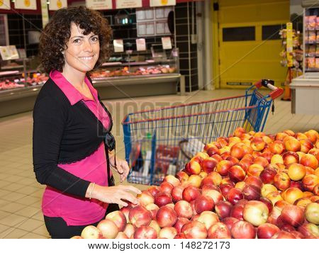 Smiling Woman Shopping In Supermarket Department Of Fruits And Vegetables
