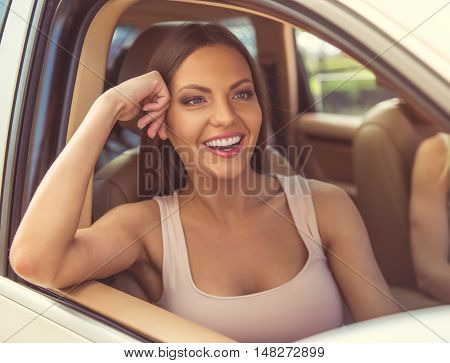 Portrait of beautiful girl looking away and smiling while sitting on the passenger seat in the car