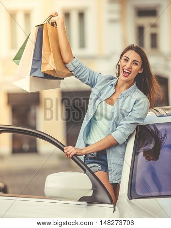 Attractive stylish girl is holding shopping bags looking at camera and smiling while leaning out the car door