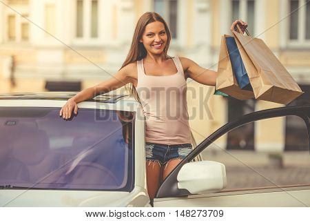 Pretty stylish girl is holding shopping bags looking at camera and smiling while leaning out the car door