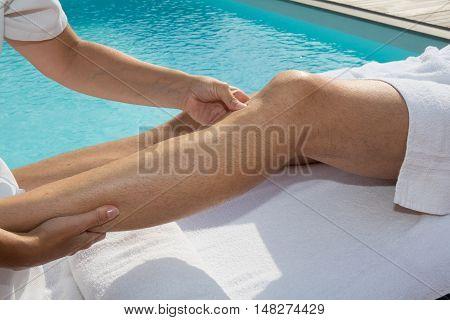 Woman Massaging The Legs Of Man Near Swimming Pool.