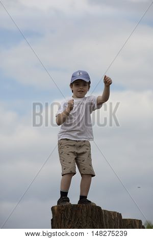 Dancing boy on pedestal. Funny white child with baseball cap. Young lad frolics on stump. Youngster rollicks on music. In captivity of dance. Son spends leisure time activities in music festival.