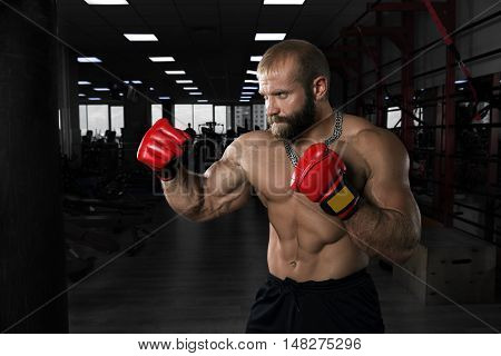 Strong muscular man training in the gym. Athlete with boxing gloves has a punching bag.