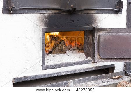 white wood oven with the door open iron and wood burning