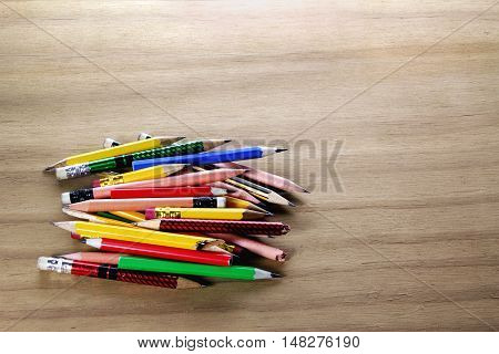 Pile of Short Pencils on Wooden Background