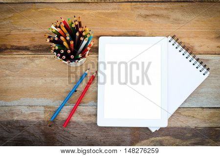Color pencils in the cups and notebook placed on a desk.