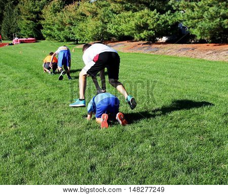 2 teams of teenage boys having a leap frog race on the grass