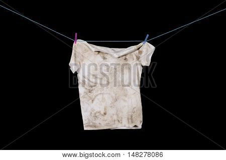 Dirty white t-shirt hanging on blue rope with blue and pink pegs. Isolate. Black background.