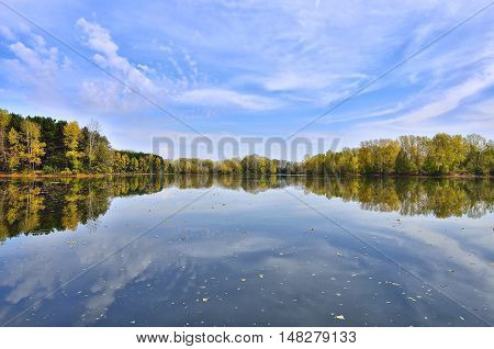 Colorful autumn landscape on the lakeside with reflection of clouds and trees on the water.