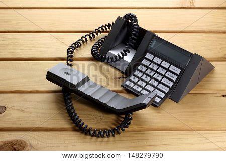Black Pushbutton Landline Telephone on Wooden Background