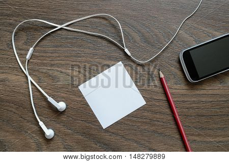 White Headphone, Paper, Phone And Pencil On Wooden Table