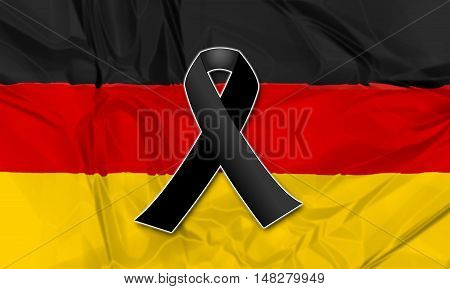 Black ribbon on flag of Germany in memory of victims of terrorist attack.