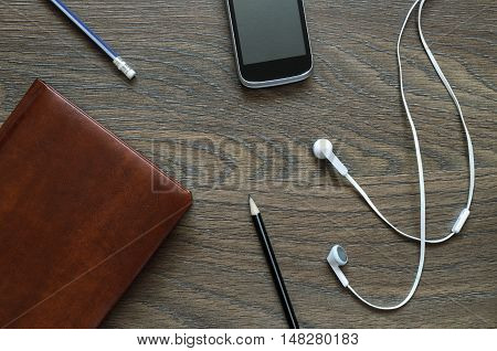 White Headphone, Notebook, Phone And Pencil On Wooden Table