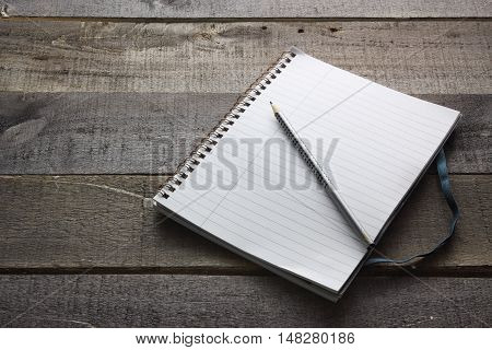 Pencil and Note Pad on Wooden Background