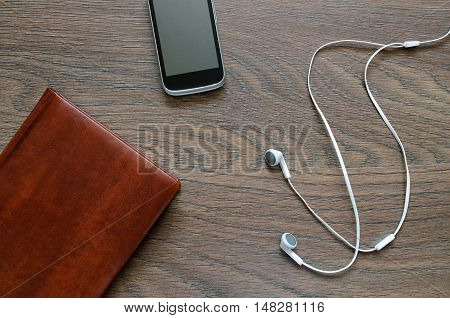 White Headphone, Notebook And Phone On Wooden Table