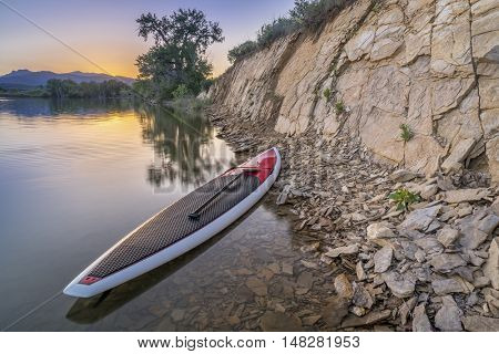 stand up paddleboard with a paddle on calm lake with a rocky cliff at dusk in northern Colorado