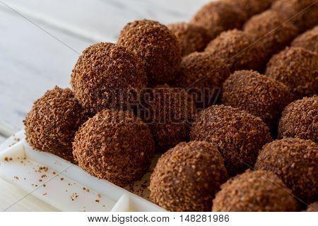 Brown ball shaped sweets. Rows of candies. Dessert from russian cuisine. Crumbled biscuits and butter.