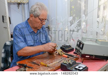 grandfather working with a soldering iron. Grandfather wearing a blue shirt. He sits on the couch. Grandpa is at home.