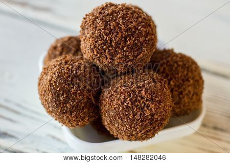 Brown candies covered in crumbs. Sweets in white bowl. Chocolate rum balls. Cocoa powder and cookies.