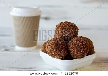 Candies and hot drink cup. Brown sweets in bowl. Coffee and chocolate balls. Freshly cooked dessert in cafe.