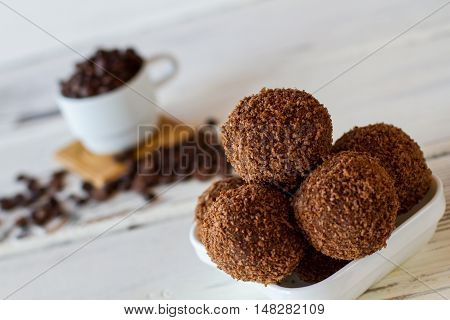 Sweets in a bowl. Brown desserts with crumbs. Delicious chocolate balls. Crumbled cookies mixed with butter.