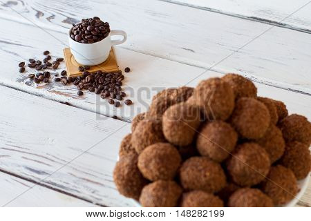 Sweets and coffee beans. White cup on wooden background. Freshly cooked rum balls. Lots of sugar and caffeine.