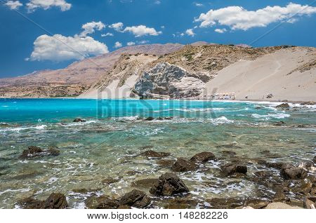 Agios Pavlos Beach in Crete island, Greece. Tourists relax and bath in crystal clear water of St. Paul Sandhill Beach.