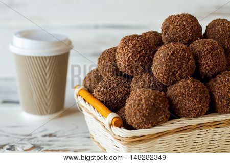 Brown sweets in wicker basket. Paper cup with lid. Tea and chocolate balls. Mixture of biscuits and cocoa.