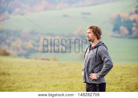 Handsome young man running outside in sunny autumn nature, resting.
